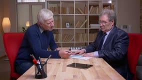 Профиль снятый старых бизнесменов сидя на таблице работая на бумагах статистики и обсуждая активно акции видеоматериалы