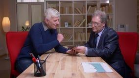Профиль снятый старых бизнесменов сидя на таблице работая совместно на проекте используя планшет сток-видео