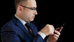 Профиль средн-достигшего возраста человека в костюме на черной предпосылке Бизнесмен касается сенсорному экрану с его пальцем видеоматериал