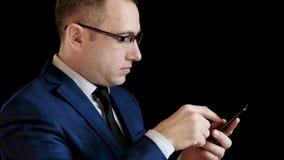 Профиль средн-достигшего возраста человека в костюме на черной предпосылке Бизнесмен работает в Интернете через его смартфон сток-видео