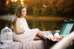 Профиль чувственной романтичной девушки, одетый в платье лета, усаженном в шлюпку с котенком в руках, во время на света захода со стоковые изображения rf