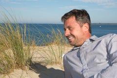 Профилируйте взгляд бизнесмена сидя и работая на пляже Стоковое Фото