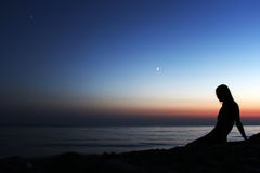 Профилируйте силуэт женщины смотря на пляже на заходе солнца Стоковое Изображение RF