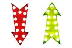 Профи - и - жулики: красный цвет вниз и зеленый цвет вверх по винтажным ретро стрелкам загоренным с электрическими лампочками Стоковое фото RF
