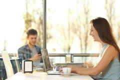 Профиль девушки используя компьтер-книжку в кофейне Стоковая Фотография RF