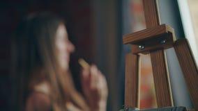 Профиль женщины из фокуса, в переднем плане деревянный мольберт сток-видео