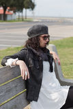 Профиль женщины сидя на скамейке в парке Стоковая Фотография