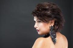 Профиль женщины с красивыми волосами и положенными шикарными черными серьгами Стоковые Изображения