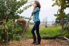 Профиль зрелой женщины с грабл и телефоном Стоковые Фотографии RF