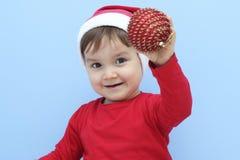 Профиль маленького ребенка одетого как Санта Клаус с красной безделушкой в его руке стоковые изображения rf