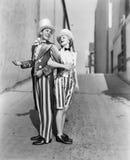 Профиль молодого человека и молодой женщины стоя с рукой в руке в костюме (все показанные люди нет более длинные живущих и нет Стоковая Фотография