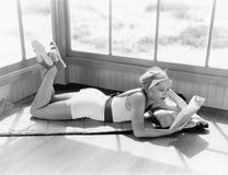 Профиль молодой женщины лежа на одеяле на ее животе и читая книгу (все показанные люди нет более длинные живущих и нет Стоковые Изображения RF