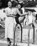 Профиль молодой женщины сидя на лестнице на стороне бассейна при другая женщина стоя за ей (все показанные люди никакие Стоковые Изображения