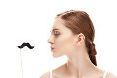 Профиль серьезной молодой женщины смотря поддельный усик на stic Стоковая Фотография RF