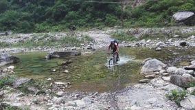 Проход глубокого брода реки горы на горном велосипеде