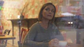Прохожие внимательной женщины наблюдая через окно ее любимой кофейни сток-видео