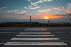 Проходить пешеходов вне города на заходе солнца Стоковая Фотография