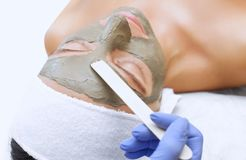 Процедура для прикладывать маску от глины к стороне красивой женщины стоковое фото rf