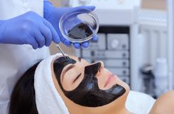 Процедура для прикладывать черную маску к стороне красивой женщины стоковое изображение rf