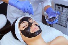 Процедура для прикладывать черную маску к стороне красивой женщины стоковые фотографии rf