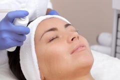 Процедура испаряться кожа стороны молодой женщины перед очищать кожу стоковые фотографии rf