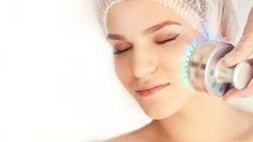 Процедура по косметологии женщины Светлая обработка стороны Медицинский ремонт кожи Анти- морщинка Skincare цвета стоковое изображение