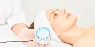 Процедура по косметологии Skincare лицевая Сторона женщины красоты Голубая светлая медицинская терапия Рука специалиста стоковые изображения