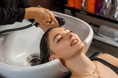Процедура по стирки Красивая молодая женщина с головой парикмахера моя на парикмахерской стоковое фото rf