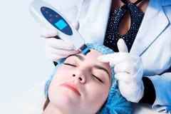 Процедура ультразвуковой чистки стороны Медицинское лечение и забота кожи Доктор-cosmetologist делает прибором процедуру стоковые фото
