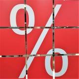 Проценты знака на красной предпосылке, надписи белого цвета, оно разделено в квадраты, стоковое изображение