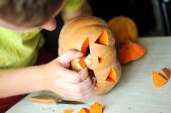 Процесс вырезывания тыквы хеллоуина, процесс делать Джек-o-фонарик Мужские руки с ножом Стоковое Изображение RF