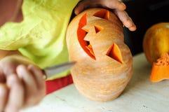 Процесс вырезывания тыквы хеллоуина, процесс делать Джек-o-фонарик Мужские руки с ножом Стоковая Фотография RF