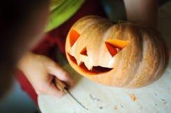 Процесс вырезывания тыквы хеллоуина, процесс делать Джек-o-фонарик Мужские руки с ножом Стоковое фото RF