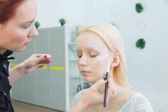 Процесс делать макияж Художник макияжа работая с щеткой на модельной стороне стоковые изображения rf