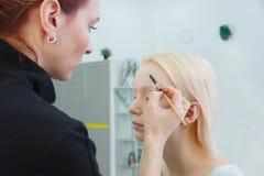 Процесс делать макияж Художник макияжа работая с щеткой на модельной стороне стоковые фото