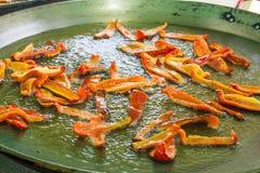 Процесс жарить куски жарки красных capsicums болгарских перцев в горячем горячем оливковом масле Большой плоский лоток паэлья или Стоковое Фото