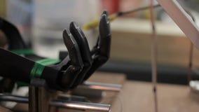 Процесс изгибать искусственную механически руку в медицинской лаборатории внутри помещения