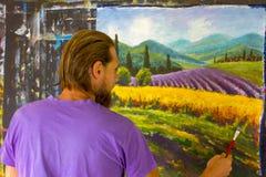 Процесс искусства творческий Художник создает крася итальянскую сельскую местность лета Тоскана Поле красных маков, поле желтой р Стоковые Фотографии RF