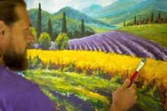 Процесс искусства творческий Художник создает крася итальянскую сельскую местность лета Тоскана Поле красных маков, поле желтой р Стоковые Изображения RF