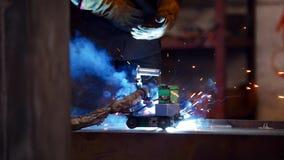Процесс конструкции Человек на заводе конструкции используя сварочный аппарат Яркое голубое освещение стоковые фото