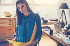 Процесс конторской работы просторной квартиры Молодая женщина при обработка документов стоя в открытом пространстве Стоковая Фотография