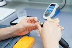 Процесс молоть челюсть во время продукции Зубоврачебный техник обрабатывает искусственные зубы с micromotor стоковое фото rf