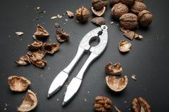 Процесс открытия ядра грецкого ореха и всех грецких орехов на черной предпосылке стоковое изображение