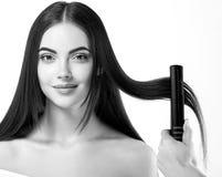 Процесс парикмахерских услуг Волосы девушки модельные выправляя утюги Beauti стоковая фотография rf