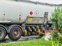 Процесс перевозки горючего от тележки танка в резервуар газа бензоколонки Взгляд со стороны следа танка и соединенного шланга стоковое изображение rf