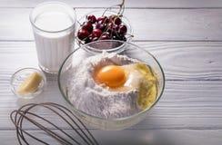 Процесс подготовки пирога вишни Конец вверх по ингридиентам - молоко, масло, яичко, мука, вишня на белой деревянной предпосылке Стоковые Фото