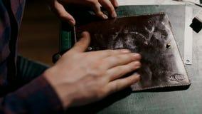 Процесс производства кожаный бумажник handmade Ремесленник кладет размягчая гель на законченный продукт сток-видео