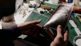 Процесс производства кожаный бумажник handmade Ремесленник кладет размягчая гель на законченный продукт акции видеоматериалы
