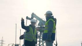 Процесс разговора 2 работников около оборудования извлечения масла сток-видео