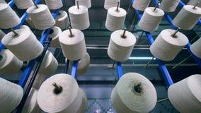 Процесс свертывать спиралью потоки на катушкы на особенном шкафе на фабрике ткани видеоматериал